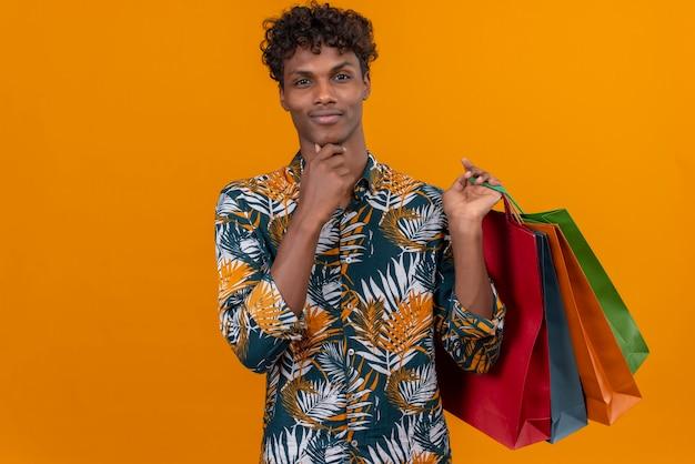 Denkende jonge knappe donkerhuidige man met krullend haar in bladeren bedrukt overhemd glimlachend boodschappentassen vasthouden met hand op kin terwijl staande op een oranje achtergrond