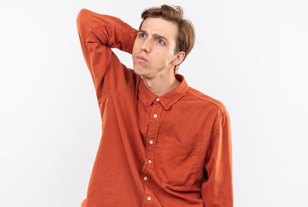 Denkende jonge knappe kerel die een rood overhemd draagt dat hand op hals legt die op witte muur wordt geïsoleerd