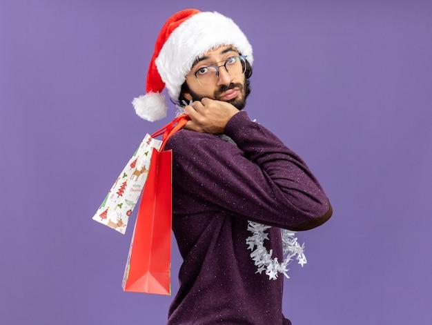 Denkende jonge knappe kerel die kerstmishoed met slinger op hals draagt die giftzakken op schouder houdt die op blauwe achtergrond wordt geïsoleerd