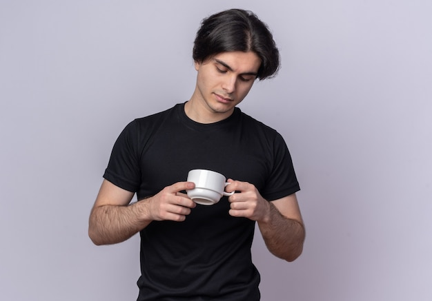 Denkende jonge knappe kerel die zwarte t-shirt draagt ?? die en kop van koffie bekijkt die op witte muur wordt geïsoleerd