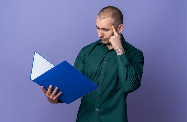 Denkende jonge knappe man met een groen shirt die de map vasthoudt en bekijkt