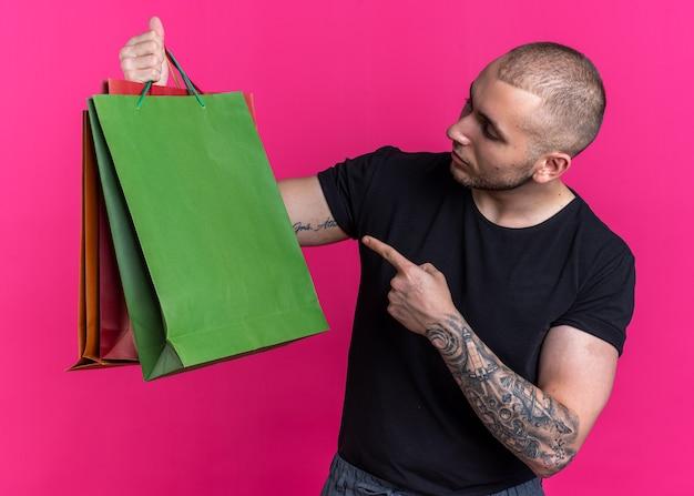Denkende jonge knappe man met een zwart t-shirt in zijn hand en wijst naar papieren zakken geïsoleerd op roze achtergrond