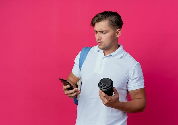 Denkende jonge knappe mannelijke student die de kop van de achterzakholding van koffie draagt