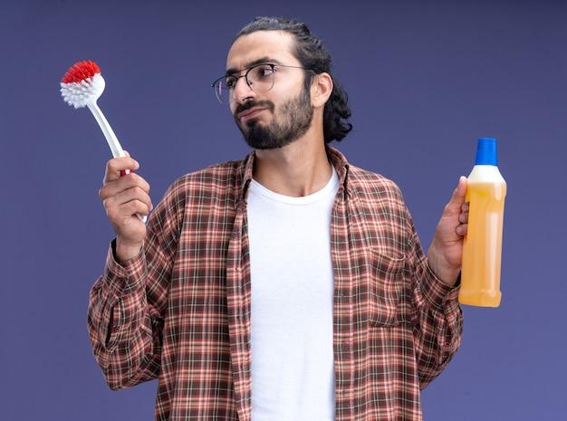 Denkende jonge knappe schoonmaakster die de borstel van de t-shirtholding met reinigingsmiddel draagt dat op blauwe muur wordt geïsoleerd