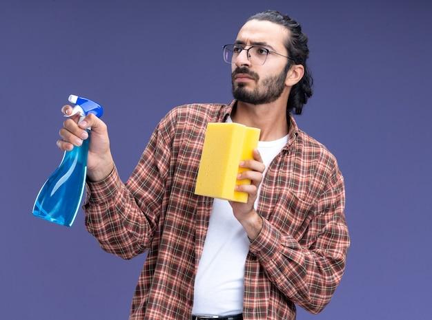 Denkende jonge knappe schoonmaakster die de spuitfles van de t-shirtholding met spons draagt die op blauwe muur wordt geïsoleerd