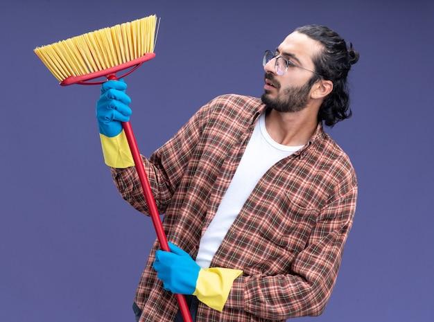 Denkende jonge knappe schoonmaakster die t-shirt en handschoenen draagt ?? die en zwabber bekijkt die op blauwe muur wordt geïsoleerd