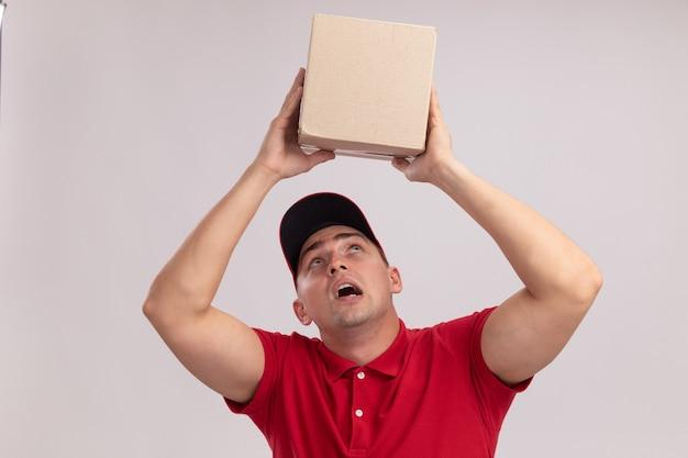 Denkende jonge leveringsmens die eenvormig met glb draagt die en doos bekijkt die op witte muur wordt geïsoleerd