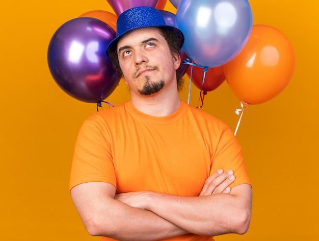 Denkende jonge man met feestmuts die vooraan staat met ballonnen die handen kruisen geïsoleerd op een oranje muur