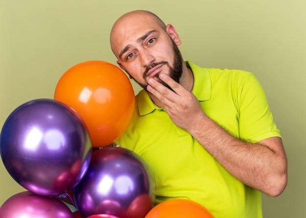 Denkende jonge man met geel t-shirt met ballonnen greep kin geïsoleerd op olijfgroene muur