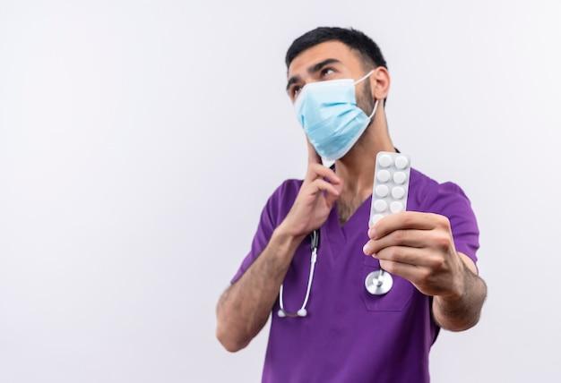 Denkende jonge mannelijke arts die paarse chirurgenkleding en een stethoscoop medisch masker draagt dat pillen op geïsoleerd wit standhoudt