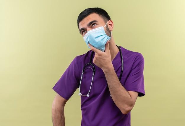 Denkende jonge mannelijke arts die paarse chirurgenkleding en een stethoscoop medisch masker draagt, legde zijn hand op de kin op geïsoleerde groene muur
