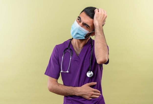 Denkende jonge mannelijke arts die paarse chirurgenkleding en een stethoscoop medisch masker draagt, legde zijn hand op het hoofd op geïsoleerde groene muur