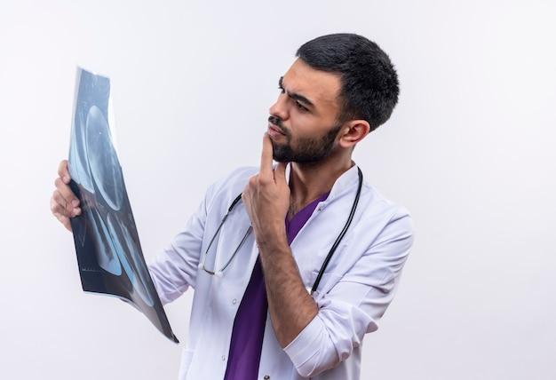 Denkende jonge mannelijke arts die stethoscoop medische toga draagt die x-ray op zijn hand op geïsoleerde wit bekijkt