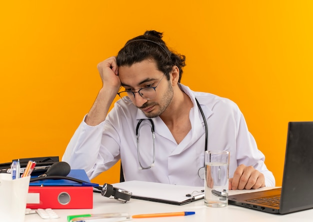 Denkende jonge mannelijke arts met een medische bril die een medische mantel draagt met een stethoscoop die aan het bureau zit