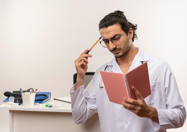 Denkende jonge mannelijke arts met een medische bril die een medische mantel draagt met een stethoscoop die voor het bureau staat