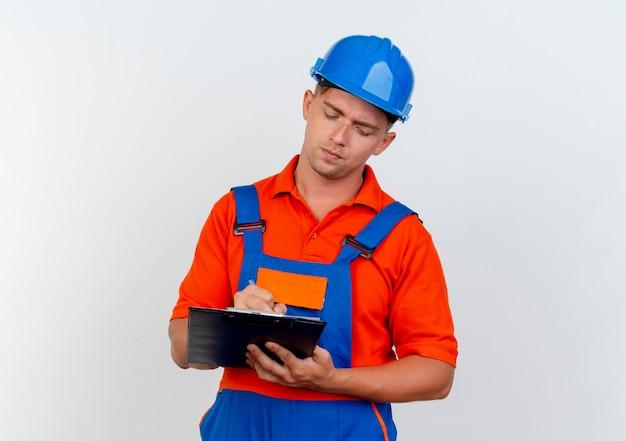 Denkende jonge mannelijke bouwer die uniform draagt en veiligheidshelm schrijft iets op klembord