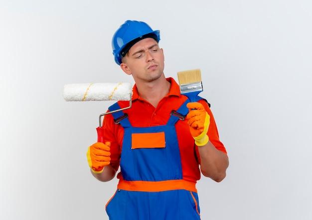 Denkende jonge mannelijke bouwer die uniform en veiligheidshelm draagt die verfroller houdt en verfborstel in zijn hand op wit bekijkt