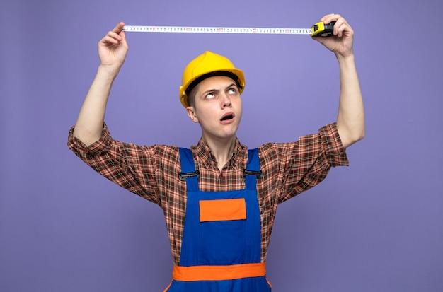 Denkende jonge mannelijke bouwer die uniform uitrekt meetlint draagt