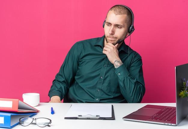 Denkende jonge mannelijke callcentermedewerker die een headset draagt die aan het bureau zit met kantoorhulpmiddelen, greep naar de kin