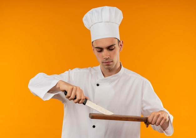 Denkende jonge mannelijke cool dragen chef-kok uniforme zoek snijplank en mes in zijn hand