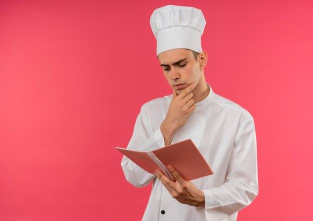 Denkende jonge mannelijke kok die eenvormige chef-kok draagt ?? en noyebook bekijkt die hand op kin met exemplaarruimte zet