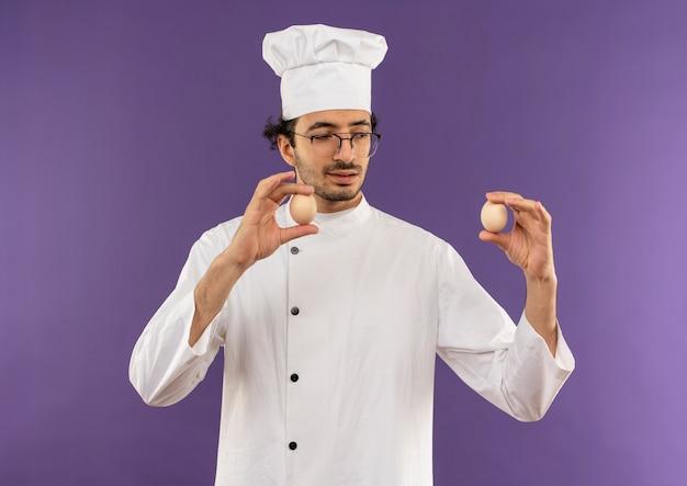 Denkende jonge mannelijke kok die eenvormige chef-kok en glazen draagt ?? die en eieren op paars houdt bekijkt