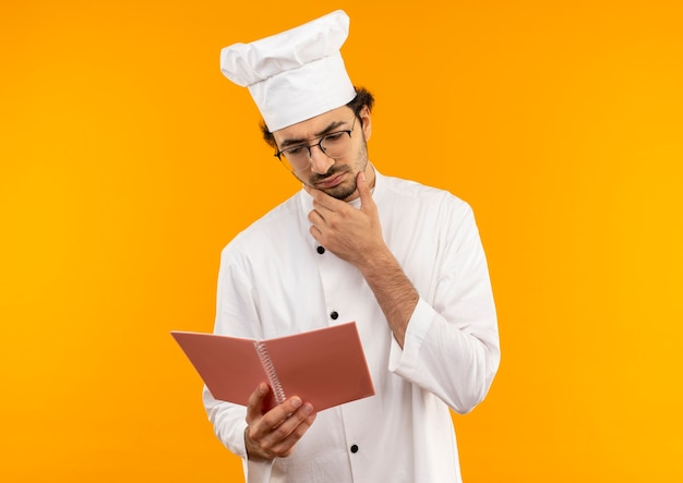 Denkende jonge mannelijke kok die eenvormige chef-kok en glazen draagt die en notitieboekje houdt bekijkt en hand op kin zet die op gele muur wordt geïsoleerd