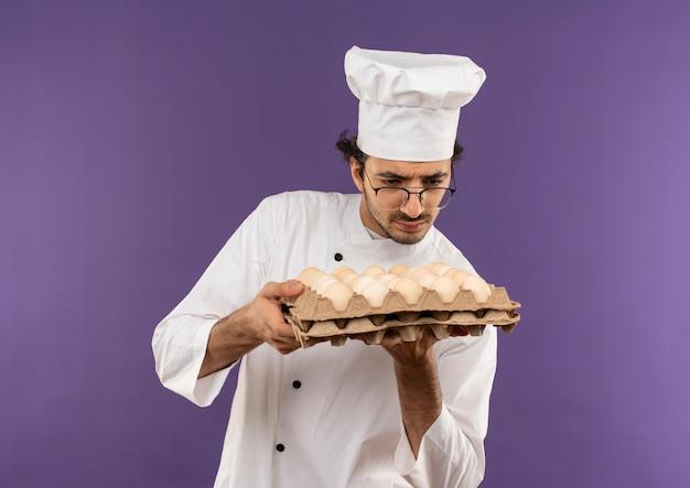Denkende jonge mannelijke kok die eenvormige chef-kok en glazen draagt ?? die en partij eieren op paars houdt bekijkt