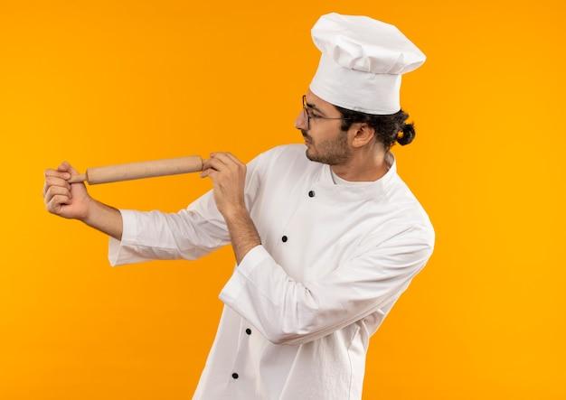 Denkende jonge mannelijke kok die eenvormige chef-kok en glazen dragen die en deegroller bekijken die op gele muur wordt geïsoleerd