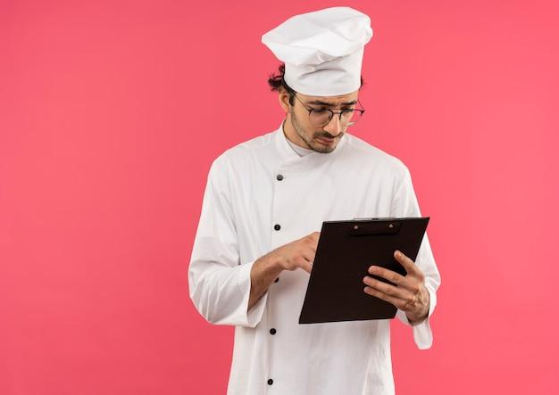 Denkende jonge mannelijke kok die eenvormige chef-kok en glazen dragen die en klembord bekijken dat op roze muur wordt geïsoleerd
