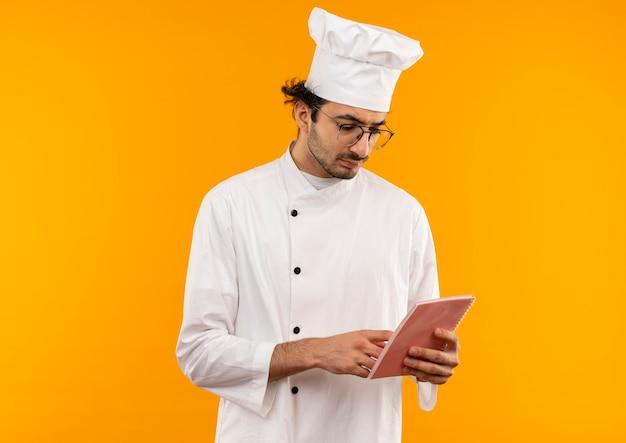 Denkende jonge mannelijke kok die eenvormige chef-kok en glazen dragen die en notitieboekje bekijken dat op gele muur wordt geïsoleerd