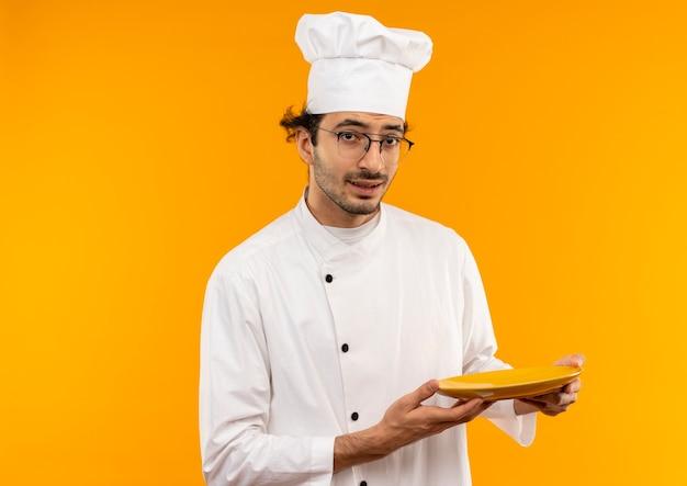 Denkende jonge mannelijke kok die eenvormige chef-kok en glazen dragen die plaat houden die op gele muur wordt geïsoleerd