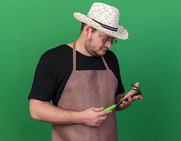 Denkende jonge mannelijke tuinman die het tuinieren hoed dragen en schoffelhark bekijken die op groene muur wordt geïsoleerd