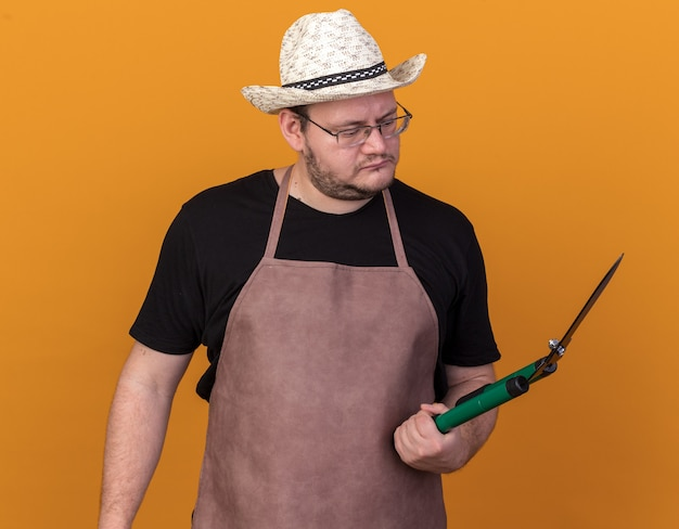 Denkende jonge mannelijke tuinman die tuinhoed en handschoenen draagt en naar tondeuses kijkt die op een oranje muur zijn geïsoleerd