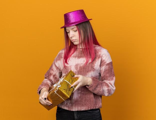 Denkende jonge mooie vrouw die een feesthoed draagt en naar een geschenkdoos kijkt die op een oranje muur is geïsoleerd