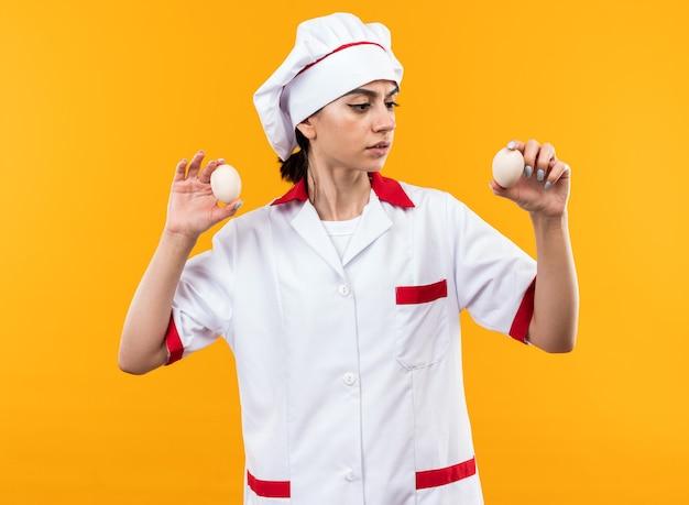 Denkende jonge mooie vrouw in chef-kok uniform houden en kijken naar eieren geïsoleerd op oranje muur