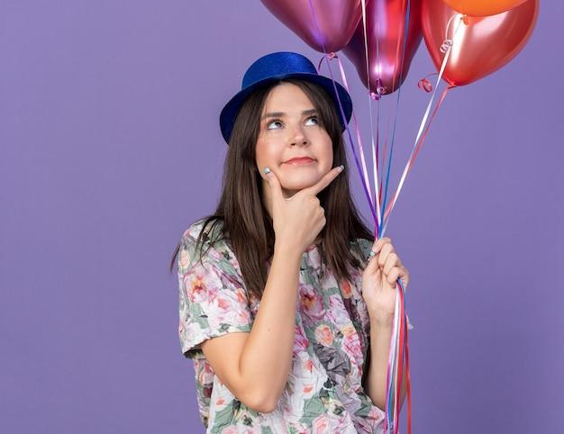 Denkende jonge mooie vrouw met feestmuts die ballonnen vasthoudt, greep kin geïsoleerd op blauwe muur