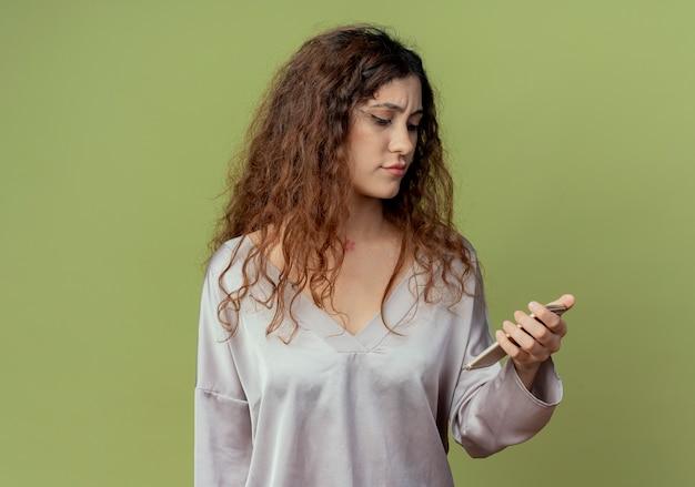 Denkende jonge mooie vrouwelijke kantoormedewerker houden en kijken naar telefoon geïsoleerd op olijfgroene muur
