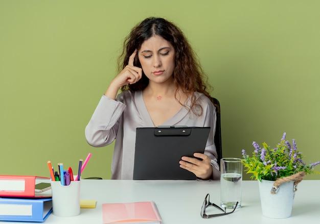 Denkende jonge mooie vrouwelijke kantoormedewerker zittend aan een bureau met kantoorhulpmiddelen vasthouden en kijken naar klembord en vinger op het hoofd zetten geïsoleerd op olijfmuur