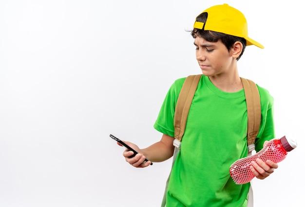 Denkende jonge schooljongen die een rugzak draagt met een dop die een waterfles vasthoudt en naar de telefoon in zijn hand kijkt