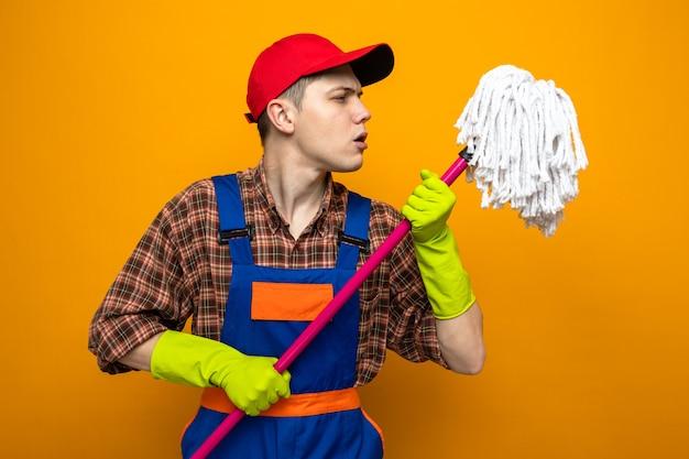 Denkende jonge schoonmaakster die uniform en pet draagt met handschoenen die de dweil vasthouden en bekijken