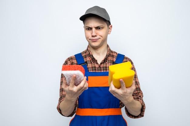 Denkende jonge schoonmaakster met uniform en pet die sponzen vasthoudt en bekijkt