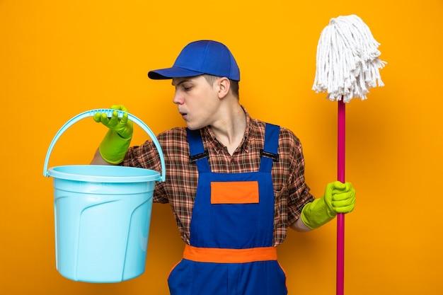 Denkende jonge schoonmaakster met uniform en pet met handschoenen die een dweil vasthoudt en naar een emmer in zijn hand kijkt