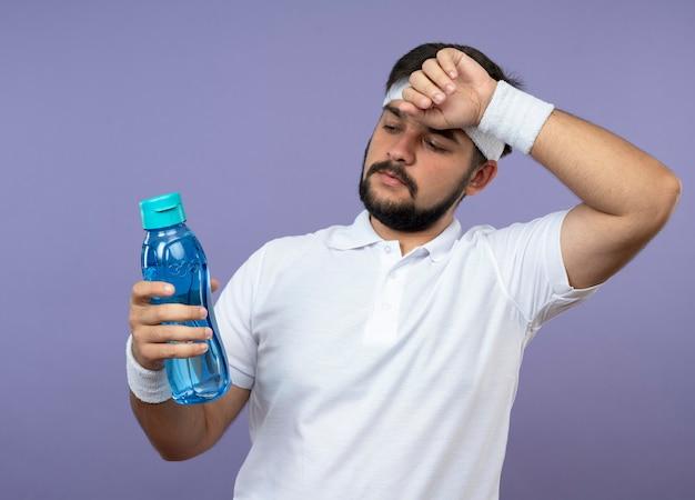 Denkende jonge sportieve man met hoofdband en polsbandje houden en kijken naar waterfles hand op voorhoofd zetten geïsoleerd op groene muur