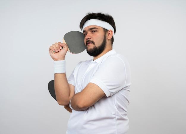 Denkende jonge sportieve mens die kant bekijkt die hoofdband en polsband draagt die pingpongracket rond gezicht houden dat op witte muur wordt geïsoleerd