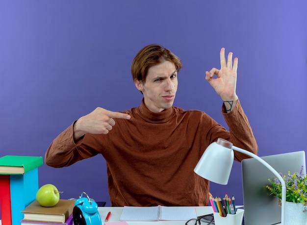 Denkende jonge studend jongenszitting bij bureau met schoolhulpmiddelen die ok gebaar en punten op paars tonen