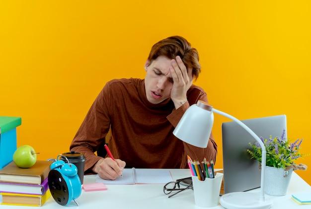 Denkende jonge studentenjongen zittend aan een bureau met schoolhulpmiddelen die iets schrijven hand op het hoofd zetten geïsoleerd op gele muur