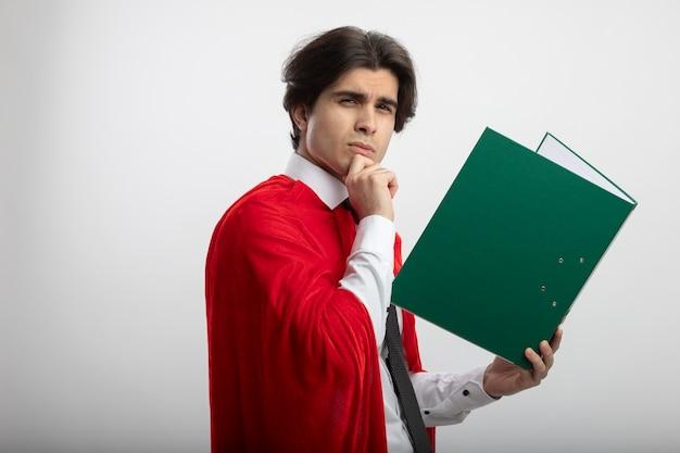 Denkende jonge superheld man met stropdas met klembord en greep kin geïsoleerd op een witte achtergrond