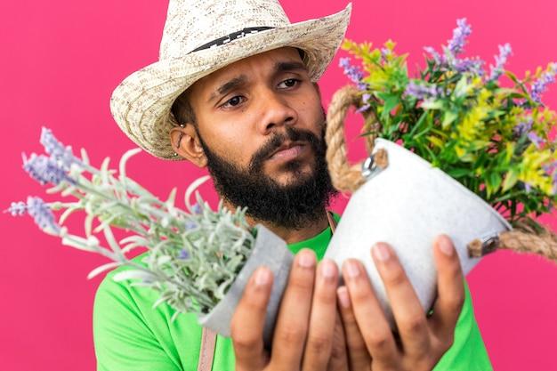 Denkende jonge tuinman afro-amerikaanse man die een tuinhoed draagt en naar bloemen in een bloempot kijkt