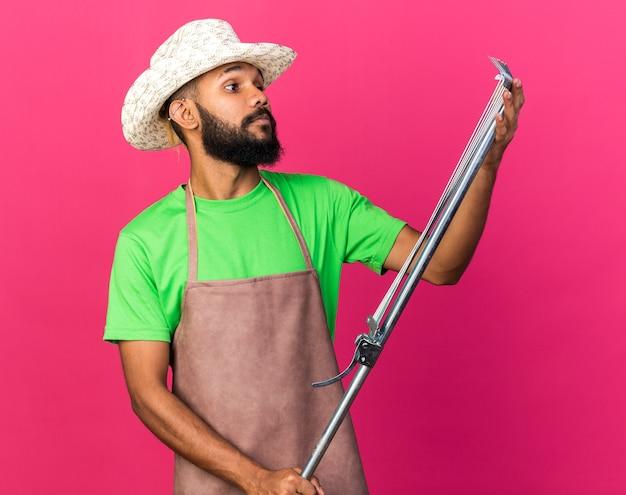 Denkende jonge tuinman afro-amerikaanse man met een tuinhoed die bladhark vasthoudt en kijkt
